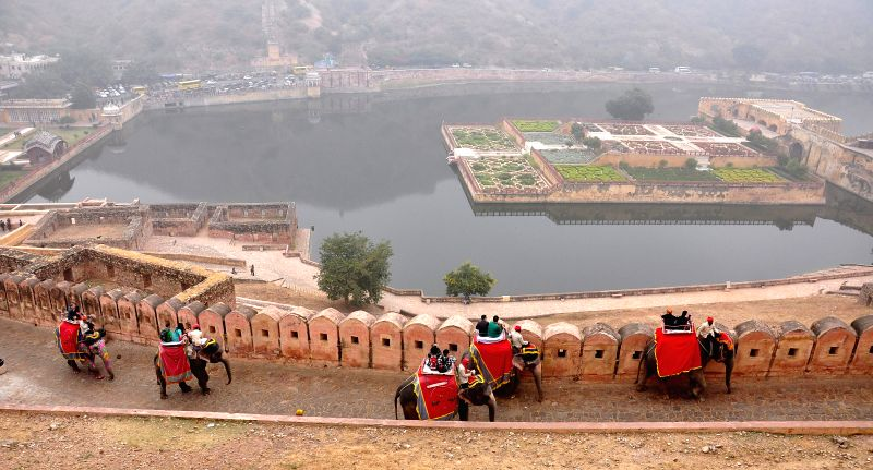 Foreign tourists enjoy an elephant ride on a chilly morning at the historic Amber Fort in Jaipur, on Dec 15, 2014.