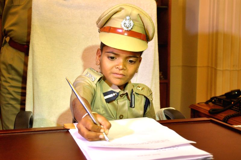 Girish Sharma, a 10-year-old boy suffering from chronic kidney disease, sits on the  chair of Jaipur police commissioner for the day on April 30, 2015. - Girish Sharma
