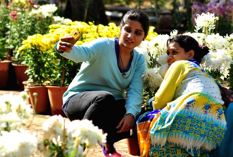 Girls click a `selfie` at a flower exhibition organised at Rajasthan University in Jaipur, on Dec 5, 2014.