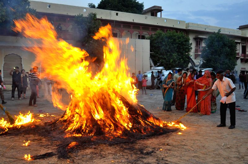 People participate in `Holika Dahan` - burning of the devil on the eve Holi at the City Palace in Jaipur, on March 5, 2015.