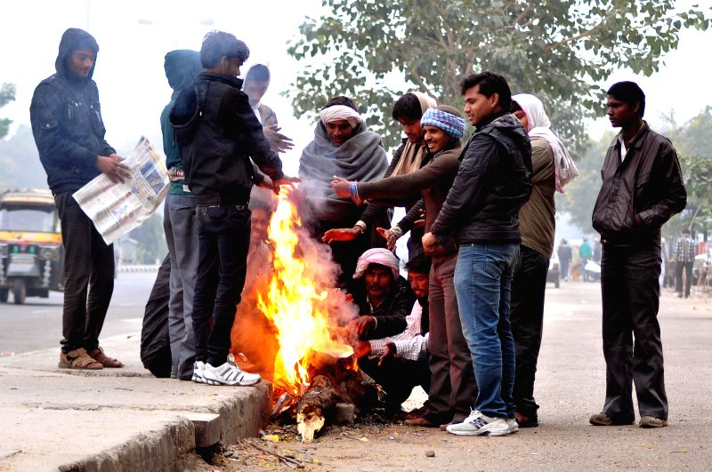 People warm themselves around a fire on a cold winter morning in Jaipur on Dec 14, 2014.