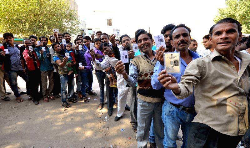 Peoples show their voter ID cards as they wait in a queue to cast their vote for local municipal elections in Jaipur, on Nov 22, 2014.