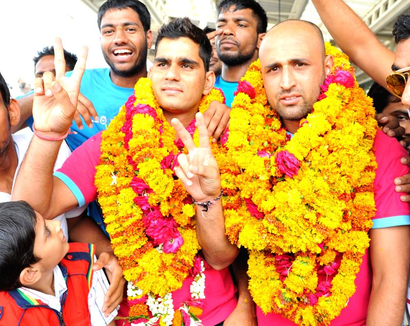 Jaipur Pink Panthers players Navneet Gautam and Raju Lal being welcomed on their arrival at Sanganer Airport, Jaipur on Sept 1, 2014. Jaipur Pink Panthers won the Pro Kabaddi final match against U ...