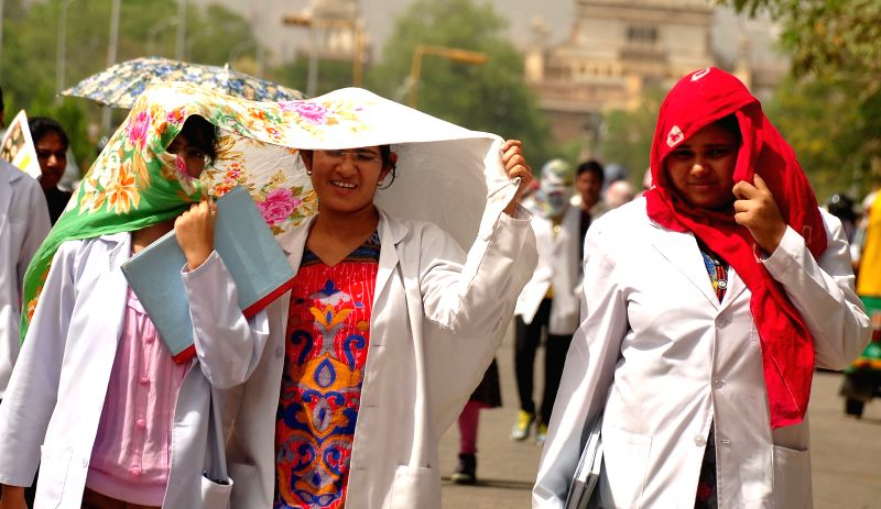 Women cover their faces as they walk in scorching sun in Jaipur on May 2, 2015.