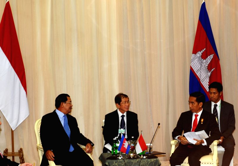 Indonesian President Joko Widodo (2nd R) talks with Cambodian Prime Minister Hun Sen (L) during a bilateral meeting on the sidelines of the Asian African Business ... - Hun Sen