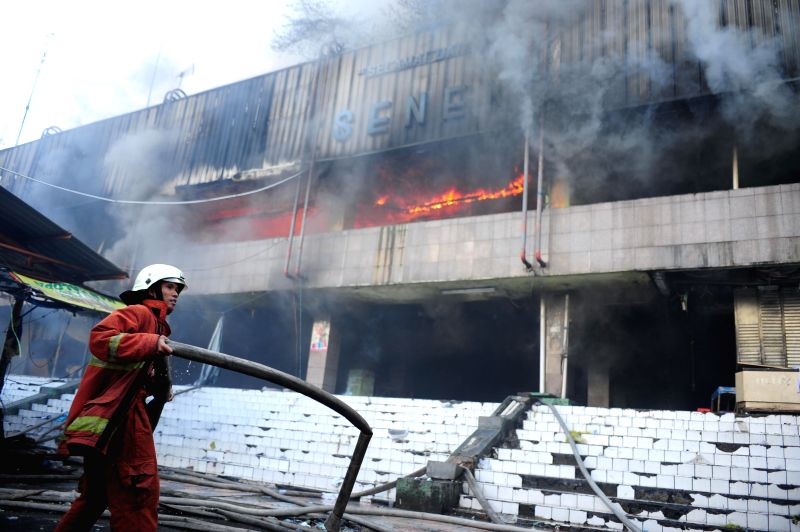 An Indonesian firefighter tries to extinguish a fire at Pasar Senen traditional market in Jakarta, Indonesia, April 25, 2014. Thousands of kiosks in a building of .