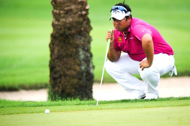 Kiradech Aphibarnrat of Thailand measures the direction before hitting the ball in the hole 18 during day 3 of CIMB Niaga Indonesian Masters at Royale Jakarta Golf