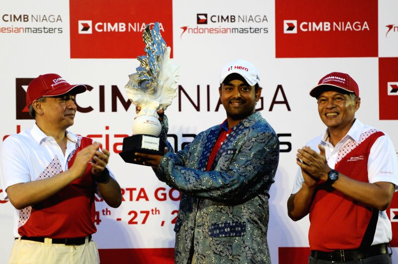Anirban Lahiri (C) of India poses with the trophy after winning the CIMB Niaga Indonesian Masters at Royale Jakarta Golf Club in Jakarta, Indonesia, April 27, ...