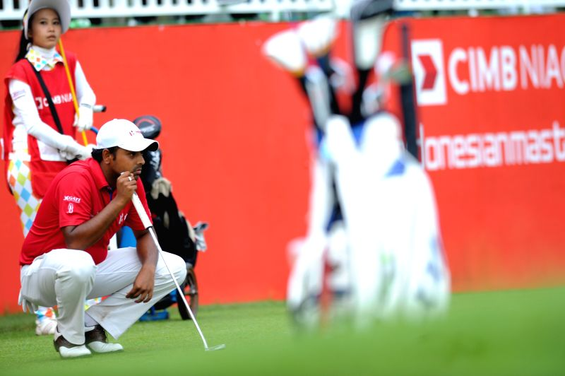 Anirban Lahiri of India measures the ball direction before hitting the ball at the hole 18 during the final day of CIMB Niaga Indonesian Masters at Royale Jakarta .
