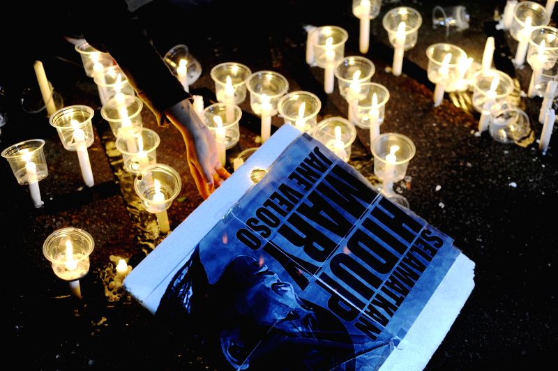 Indonesian migrant worker activists light candles during a vigil supporting Philippine national Mary Jane Fiesta Veloso who is facing execution outside the ...