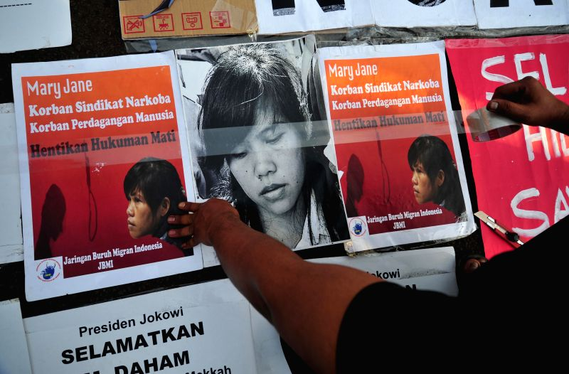 An activist prepares a picture of Philippine national Mary Jane Fiesta Veloso who faces execution during a demonstration demanding cancellation of execution ...