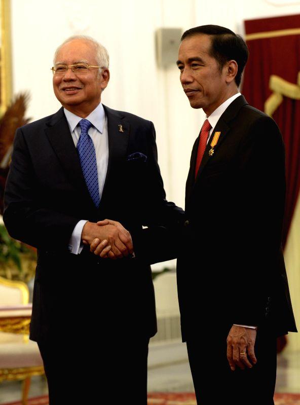 JAKARTA, Aug. 1, 2016 - Indonesian President Joko Widodo (R) shakes hands with Malaysian Prime Minister Najib Razak as they meet for the 11th Annual Consultation between Malaysia and Indonesia at ... - Najib Razak