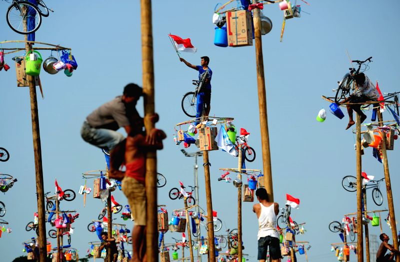 Indonesian men participate in a greased-pole climbing competition as a part of the Independence Day celebrations on Ancol beach in Jakarta, Indonesia, Aug. 17, ...