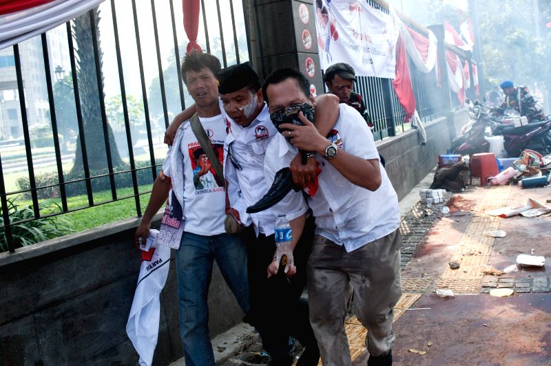 Supporters of losing presidential candidate Prabowo Subianto run to avoid tear gas fired by riot police during a rally near the constitutional court in Jakarta, ...