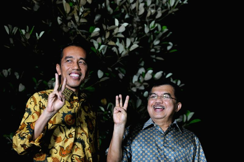 Indonesia's president-designate Joko Widodo (L) and his running mate Jusuf Kalla gesture during a press conference after the Indonesian Constitutional Court upheld .