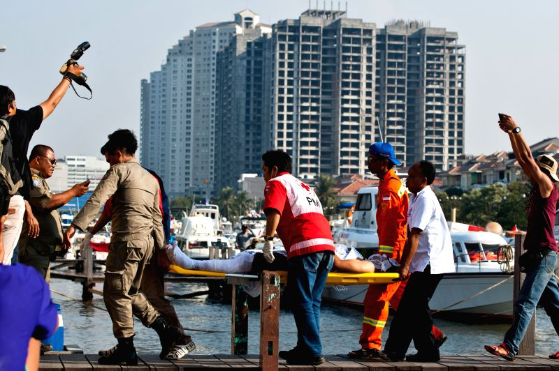 Medical team members carry a victim to an ambulance during evacuation of the passengers of KM PAUS SATU ship which burnt on the sea of Thousand Islands in Jakarta, .