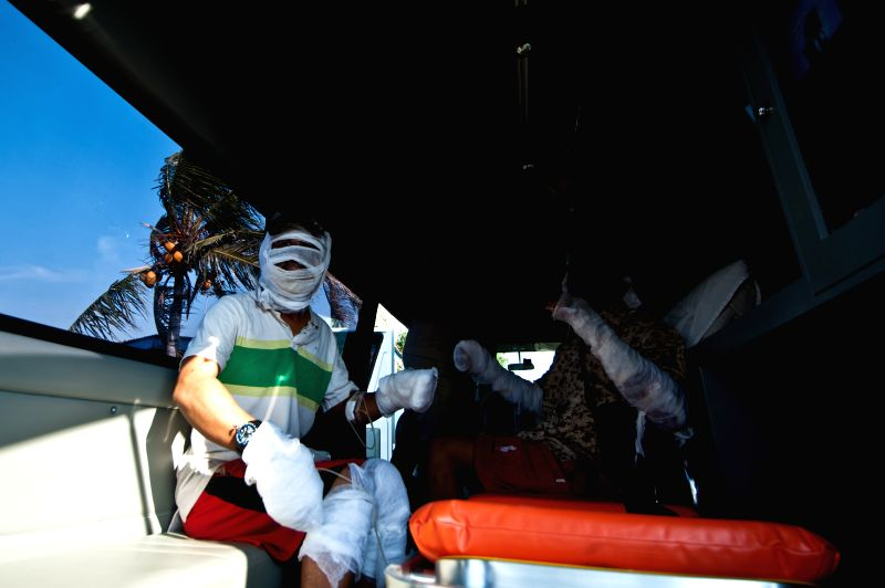 Victims are carried on an ambulance during evacuation of the passengers of KM PAUS SATU ship which burnt on the sea of Thousand Islands in Jakarta, Indonesia, Aug. .