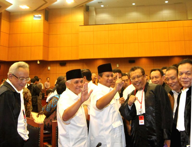 Indonesian presidential candidate Prabowo Subianto (3rd L) and his running mate Hatta Rajasa (2nd L) attend the first trial session for the election dispute case at .