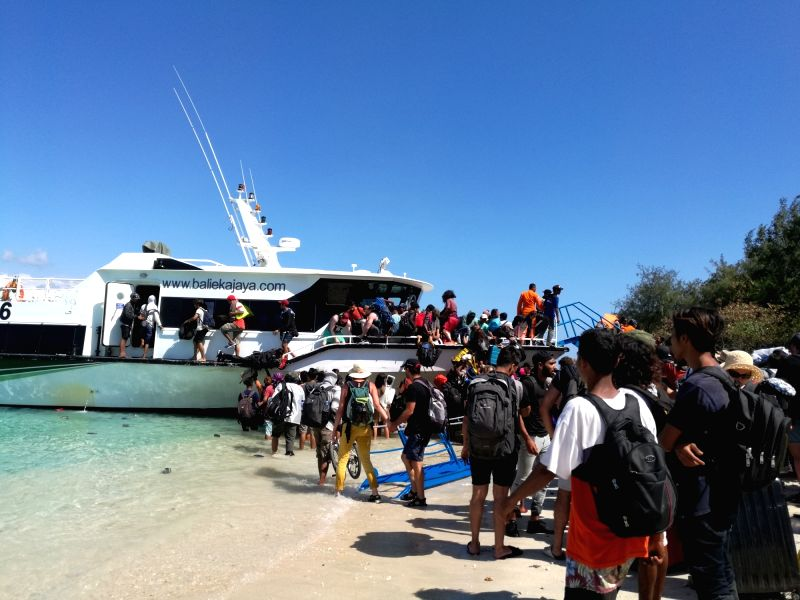 JAKARTA, Aug. 6, 2018 - Visitors evacuate from Gili Trawangan near Lombok Island in Central Indonesia, Aug. 6, 2018. The death toll rose to 91 and the number of injured people was up to 209 after a ...