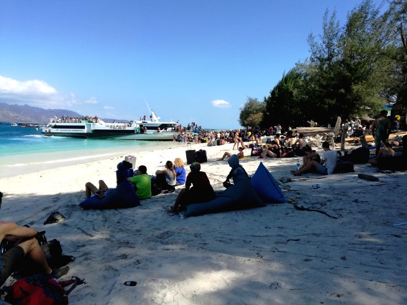 JAKARTA, Aug. 6, 2018 - Visitors wait to evacuat from Gili Trawangan near Lombok Island in Central Indonesia, Aug. 6, 2018. The death toll rose to 91 and the number of injured people was up to 209 ...