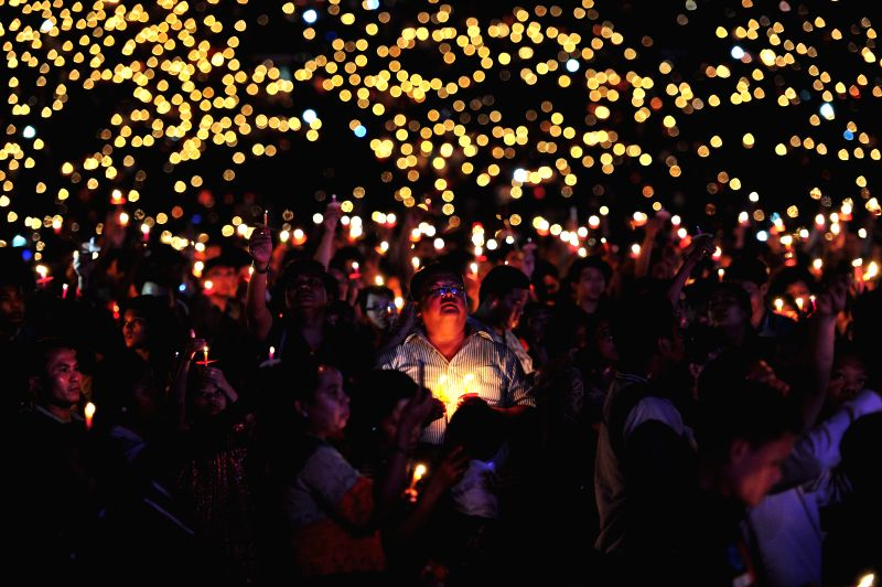 Indonesian hold candles during a Christmas mass pray at Gelora Bung Karno Stadium in Jakarta, Indonesia, Dec. 13, 2014.