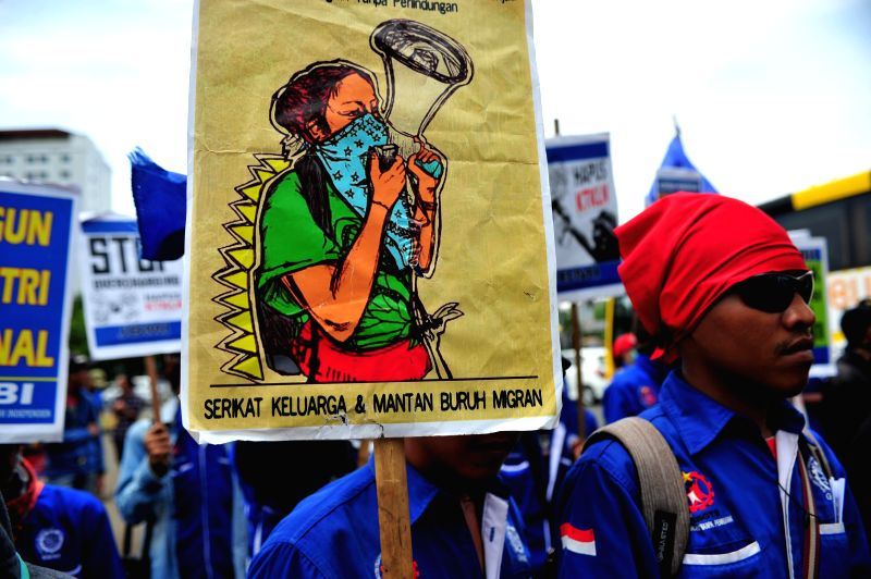 An activist from the network of Indonesian migrant workers holds a poster during a demonstration to mark the International Migrants Day in Jakarta, Indonesia, Dec. .