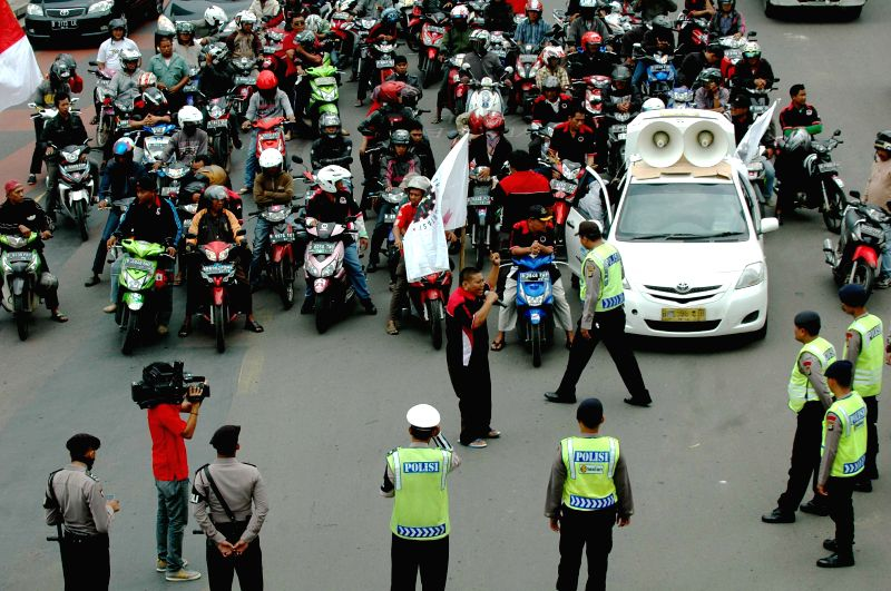 Motor bikers drive on a rally during the trial run of a new traffic regulation that bars motorcycles off main roads in Jakarta, Indonesia, Dec. 22, 2014. A pilot ...