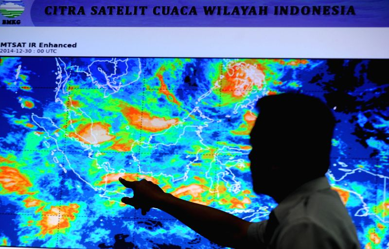 An official of Indonesia's Meteorology and Geophysics Agency points the screen of weather around Bangka-Belitung island and West Kalimantan, in Jakarta, Indonesia, .