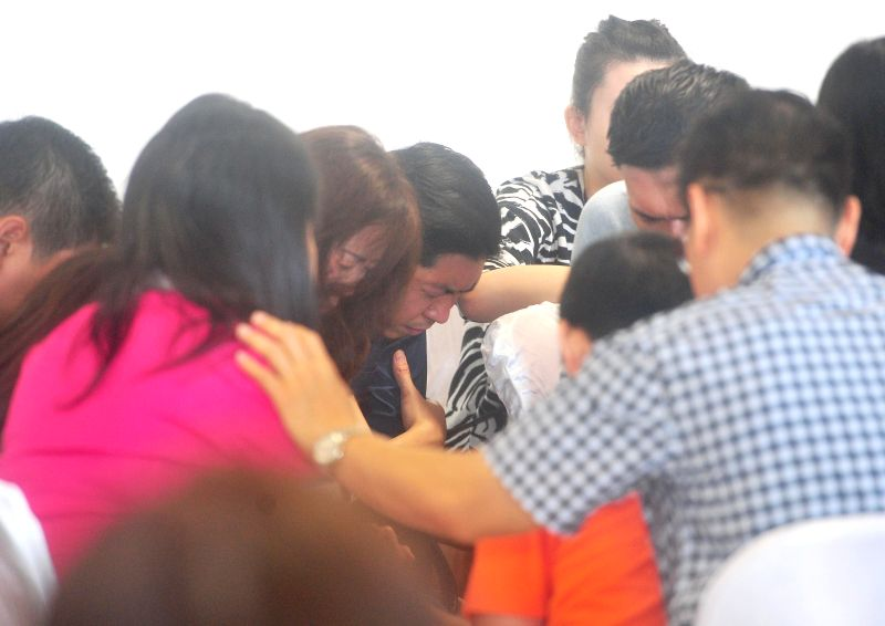 Family members of people on missing AirAsia flight QZ8501 pray together at Juanda International Airport in Surabaya, Indonesia, Dec. 30, 2014. Objects suspected of .
