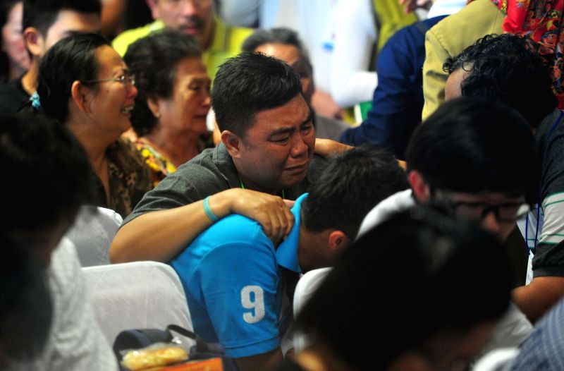Family members of people on missing AirAsia flight QZ8501 cry after hearing the announcement that the objects found in waters were confirmed parts of AirAsia QZ8501