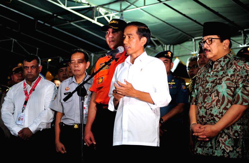 Indonesian President Joko Widodo (front) speaks to media after meeting family members of people on AirAsia flight QZ8501 at Juanda International Airport in ...