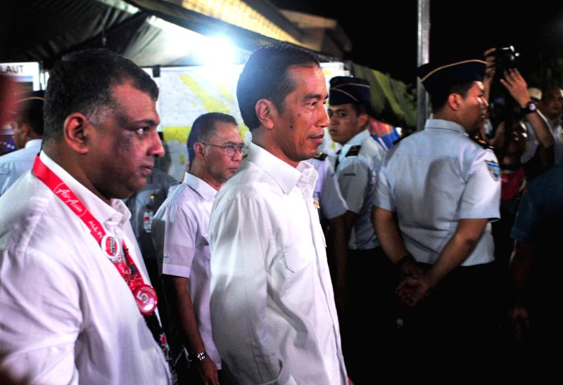 Indonesian President Joko Widodo (front R) and Tony Fernandes, group chief executive officer of AirAsia (front L), walk after meeting family members of people on ... - Tony Fernandes