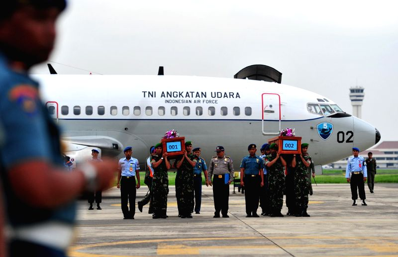 Indonesian military soldiers carry two coffins containing victims of AirAsia flight QZ8501 at Juanda Naval Air Base in Surabaya, Indonesia, Dec. 31, 2014. As many ..