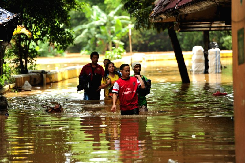 Workers walk through floodwater at Cipulir textile market in Jakarta, Indonesia, Feb. 10, 2015. Floods have paralyzed business in parts of Jakarta and forced ...