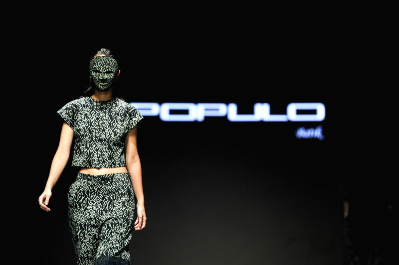 JAKARTA. Feb. 27, 2015 A model wearing a mask presents a creation by designer Populo Batik during the Indonesian Fashion Week 2015 at Jakarta Convention Center in Jakarta, Indonesia, Feb. ...