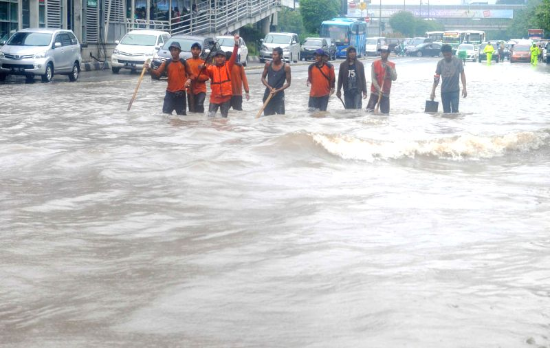 JAKARTA. Feb. 9, 2015 Workers wade through in floodwater on Thamrin street in Jakarta, Indonesia. Feb. 9, 2015. Heavy rain for a few hours flooded most of the capital region of Jakarta. ..
