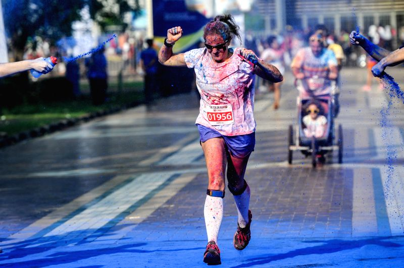 """Jakarta (Indonesia): A runner is sprinkled by color powders during a color run event in Jakarta, Indonesia, Nov. 23, 2014. Color Run, known as """"Happiest 5k on the Planet"""", is an unique run ."""