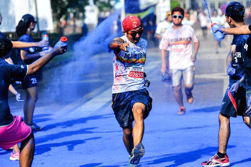 """Jakarta (Indonesia):A runner is sprinkled by color powders during a color run event in Jakarta, Indonesia, Nov. 23, 2014. Color Run, known as """"Happiest 5k on the Planet"""", is an unique run .."""
