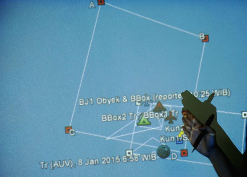 A member of Indonesian Research and Technology Application Agency points at the coordinates where signals of AirAsia flight QZ 8501 black box were detected in ...