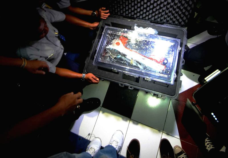 Indonesia's National Transportation Safety Committee (KNKT) members open the hardcase of Flight Data Recorder (FDR) of AirAsia Flight QZ8501 in Jakarta, Indonesia, .