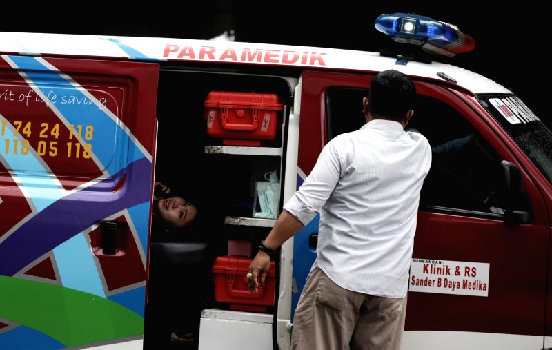 JAKARTA, Jan. 15, 2018 - An injured woman lays inside an ambulance outside the stock exchange building in Jakarta, capital of Indonesia, Jan. 15, 2018. Part of the building's first floor collapsed on ...