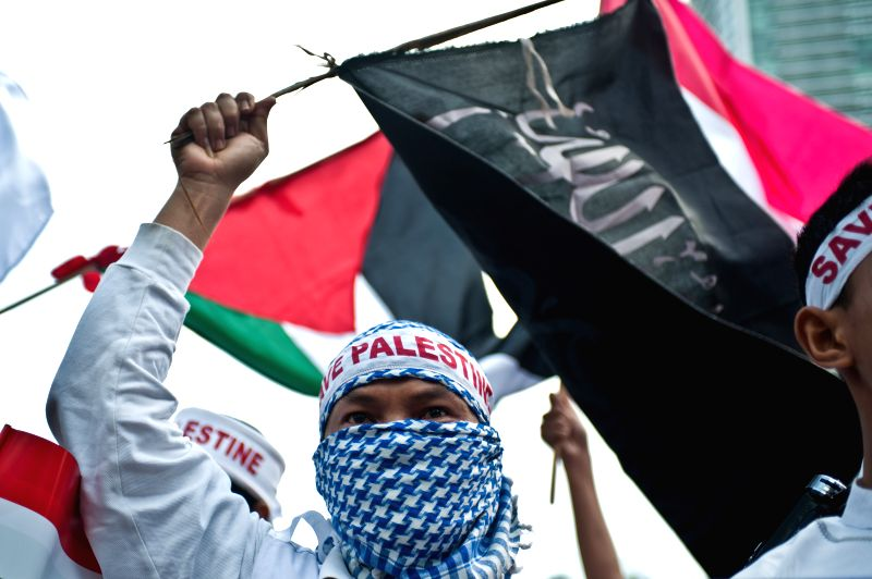 A man from Indonesian people solidarity for Palestine holds a flag during a rally to support and save Palestine in Jakarta, Indonesia, July 11, 2014. (Xinhua/Veri ..
