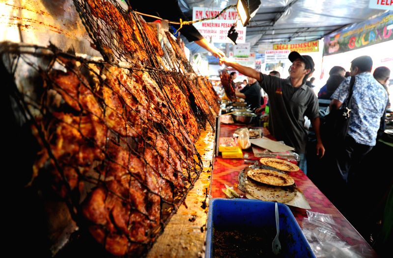 Indonesian vendors display food for iftar, the evening meal when Muslims break their fast, during the Muslim fasting month of Ramadan at a market in Jakarta, ...