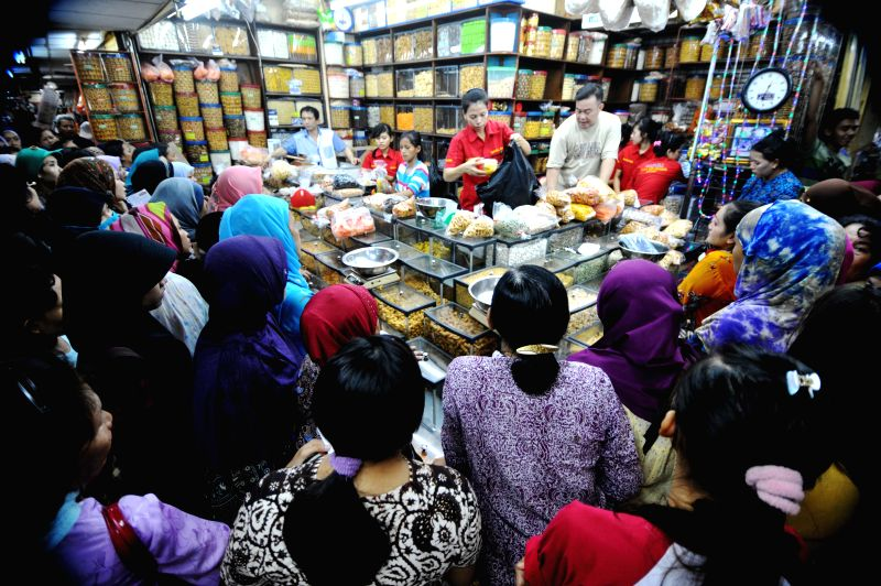 Customers select traditional cookies and snacks for the upcoming Eid al-Fitr festival at a market in Jakarta, Indonesia, July 21, 2014. People traditionally visit ..