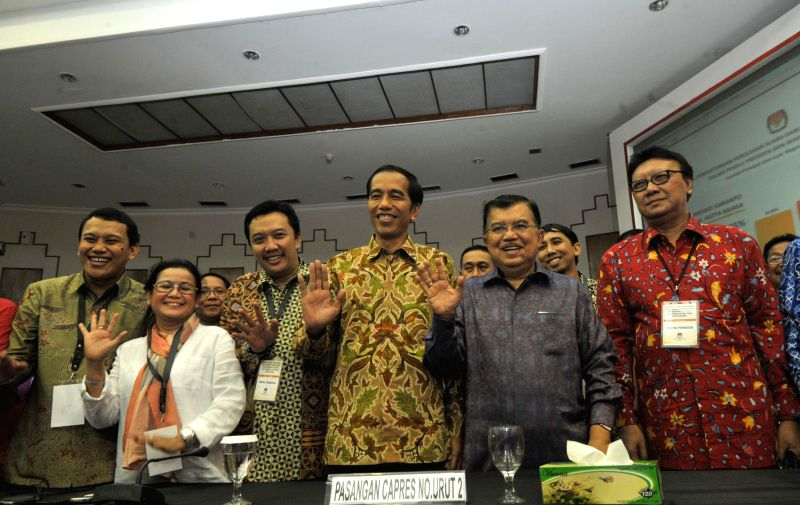 Indonesian presidential candidate Joko Widodo (3rd R) his pairing Jusuf Kalla (2nd R) greet the media after the election count announcement in Jakarta, Indonesia, ..