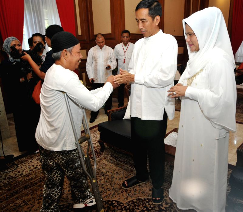 Indonesia's president-elect and Jakarta Governor, Joko Widodo (C) and his wife greet people to celebrate Eid Al Fitr at his house in Jakarta, Indonesia. ...