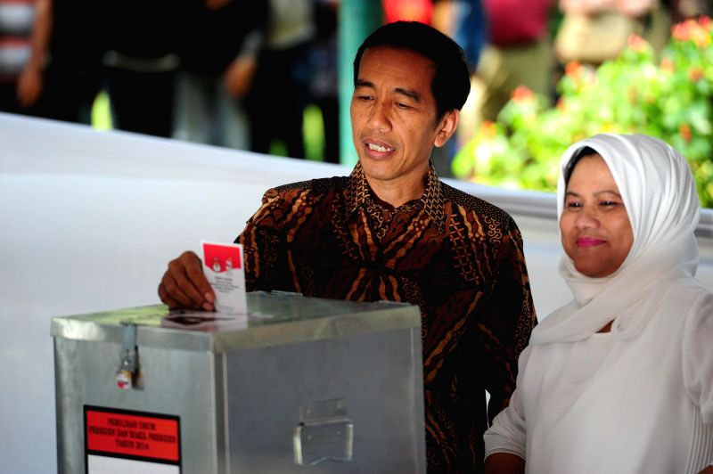 Presidential candidate of the Indonesian Democratic Party of Struggle (PDI-P) Joko Widodo (L) casts his ballot at a polling station in Jakarta, Indonesia, July 9, ...