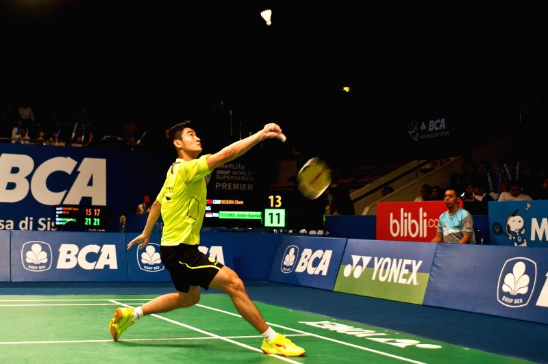 Chen Yuekun of China returns the shuttlecock to Andre Kurniawan Tedjono of Indonesia during the qualification round 2 at BCA Indonesia Open 2014 at Istora Senayan ..