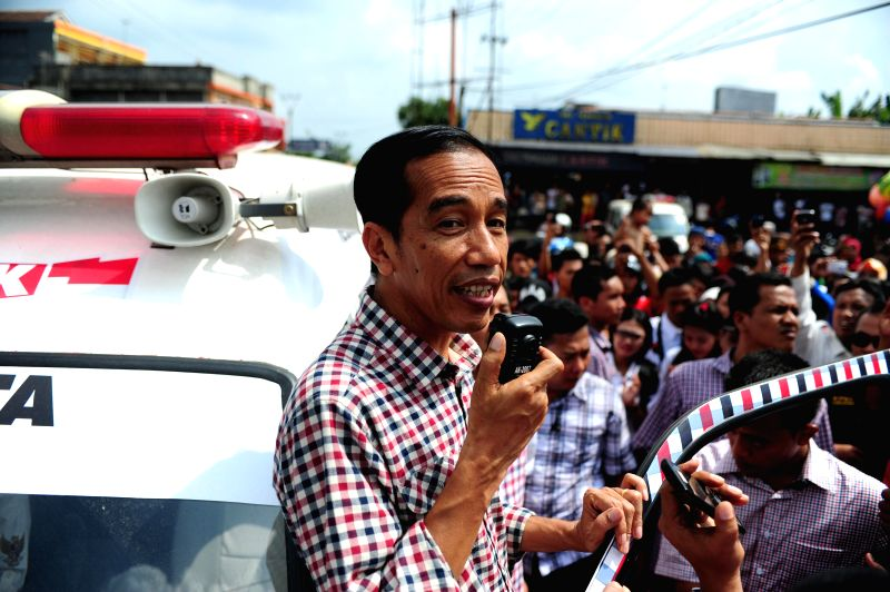 Indonesia's presidential candidate Joko Widodo (front) from the Indonesian Democratic Party of Struggle holds an ambulance speaker as he speaks during a campaign in