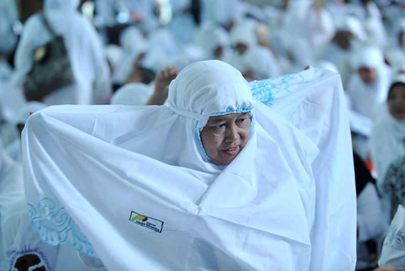 An Indonesian Muslim women wears a veil received for free to welcome the holy fasting month of Ramadan at Sunda Kelapa Mosque in Jakarta, Indonesia, June 18, 2014. .